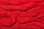 Red skeins of floss as background texture — Stock Photo