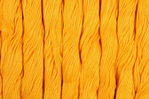 Yellow skeins of floss as background texture — Stock Photo