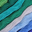Colorful skeins of floss as background texture — Stock Photo #75027257