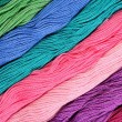 Colorful skeins of floss as background texture — Stock Photo #75027409