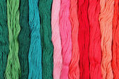 Colorful skeins of floss as background texture — Stock Photo