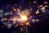 Holiday background with a sparkler — Stock Photo