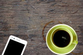 Mobile phone and coffee cup on office wooden table — Stock Photo