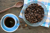 Black roasted arabica coffee beans and cup full of coffee — Stock Photo