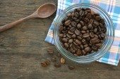 Coffee bean on wooden background with table cloth — Stock Photo