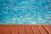 Blue swimming pool with wood flooring stripes summer vacation — Stock Photo
