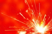 Sparkler fire on red background — Stock Photo