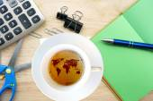 Hot coffee with worldmap and office supplies — Stock Photo