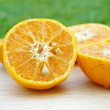 Sliced orange in close up shot with green grass as background — Stock Photo #59928127