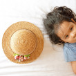 Little asian girl laying on bed with hat — Stock Photo #60830981