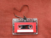 Vintage audio cassette with loose tape shaping a heart on red background — Stock Photo