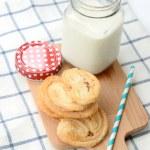 Breakfast set, glass of milk, snack on wooden plate — Stock Photo #78249574