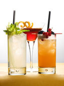 Different Drinks on Glasses with Fruits and Leaves — Stock Photo