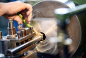Man placing lubricating oil on a lathe — Stock Photo