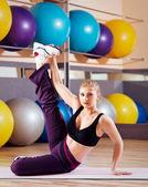Beautiful blonde performs exercises — Stock Photo