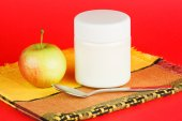 Jar with yogurt isolated on red background — Stock Photo