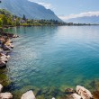 Landscape. Shore of the lake and snow capped mountains on a sunny day — Stock Photo #70964829