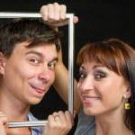 Young couple having fun making faces through frame — Stock Photo #68401887