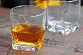 Oro marrón whisky en las rocas en un vaso — Foto de Stock