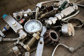 Old machine parts in machinery shop on wooden background. — Stock Photo
