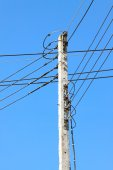 Electrical wire on pole. chaotic wire with nest on pole and blue sky background — Stock Photo