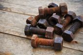 Old bolts or dirty bolts on wooden background, Machine equipment in industry work. — Stock Photo