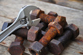Old bolts with adjustable wrench tools on wooden background. — Stock Photo