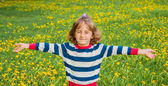 Child on the lawn with dandelions — Stock Photo