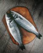 Raw seabass fish on the wooden board — Stock Photo