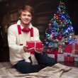 Young smiling man holding red christmas gift — Stock Photo #51896155
