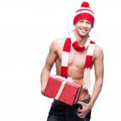 Sexy macho holding red gift — Stock Photo