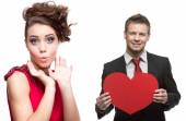 Young surprised woman and handsome man holding red heart on whit — Stock Photo