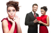 Young surprised woman and couple holding red heart on white back — Stock Photo