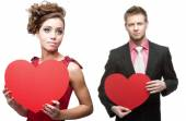 Young sensual woman and handsome man holding red heart on white — Stock Photo