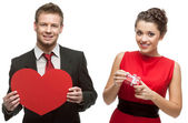 Young handsome man holding red heart and smiling woman holding g — Stock Photo