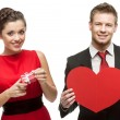 Young smiling woman and handsome man holding red heart on white — Stock Photo #53844865