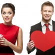 Young smiling woman and handsome man holding red heart on white  — Stock Photo #53844885