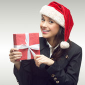 Business woman in santa hat holding gift — Stock Photo