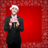 Businessman in santa hat holding gift — Stock Photo