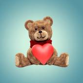 Teddy bear toy sitting, holding heart — Stock Photo