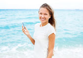 Girl using mobile phone device on the beach — Stock Photo