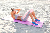 Girl working out on the beach — Stock Photo