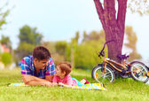 Father and son relaxing after bicycle ride in city park — Stock Photo