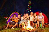 Happy kids singing songs around camp fire — Stock Photo