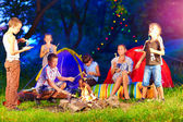 Happy kids around bonfire in summer camp — Stock Photo