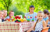Happy kids around picnic table — Stock Photo