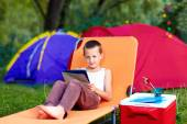 Young boy in summer camp, relaxing with tablet — Stock Photo