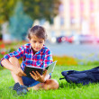 Boy, schoolkid reading book in colorful park — Stock Photo #52436961
