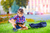 Boy, schoolkid reading book in colorful park — Stockfoto