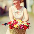 Summer flower bouquet in bicycle basket, elegant lady on background — Stock Photo #52632837